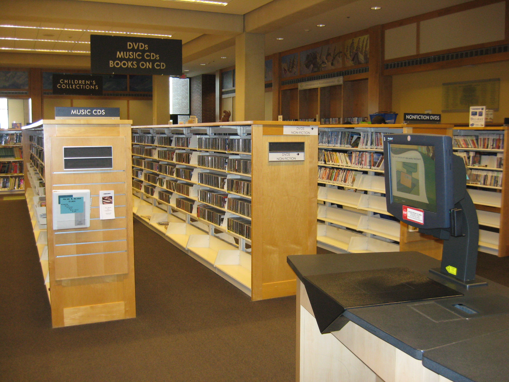 Image of self check-out stations and DVDs and CDs available for check out