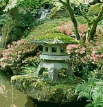 A Japanese lantern sits near the water surrounded by flowering shrubs.