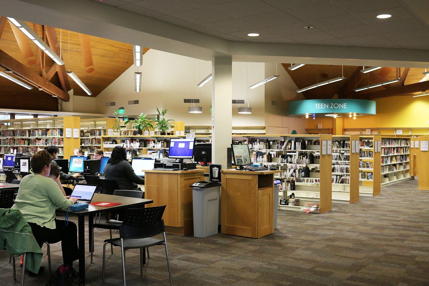 Photo of the inside of a library building with people using computers.