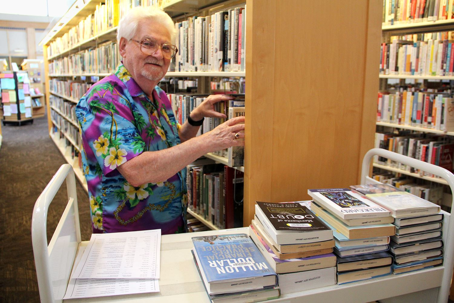 Photo of an older man shelving books inside a library.