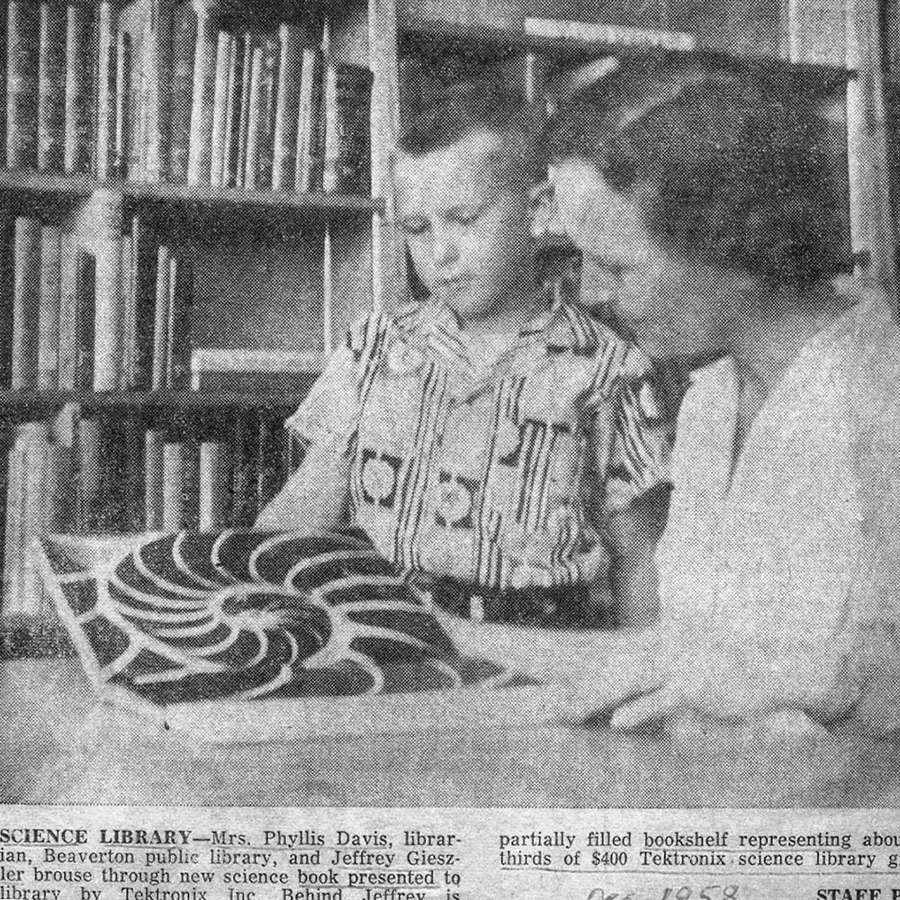 Photo from a newspaper of a young woman helping a boy read.