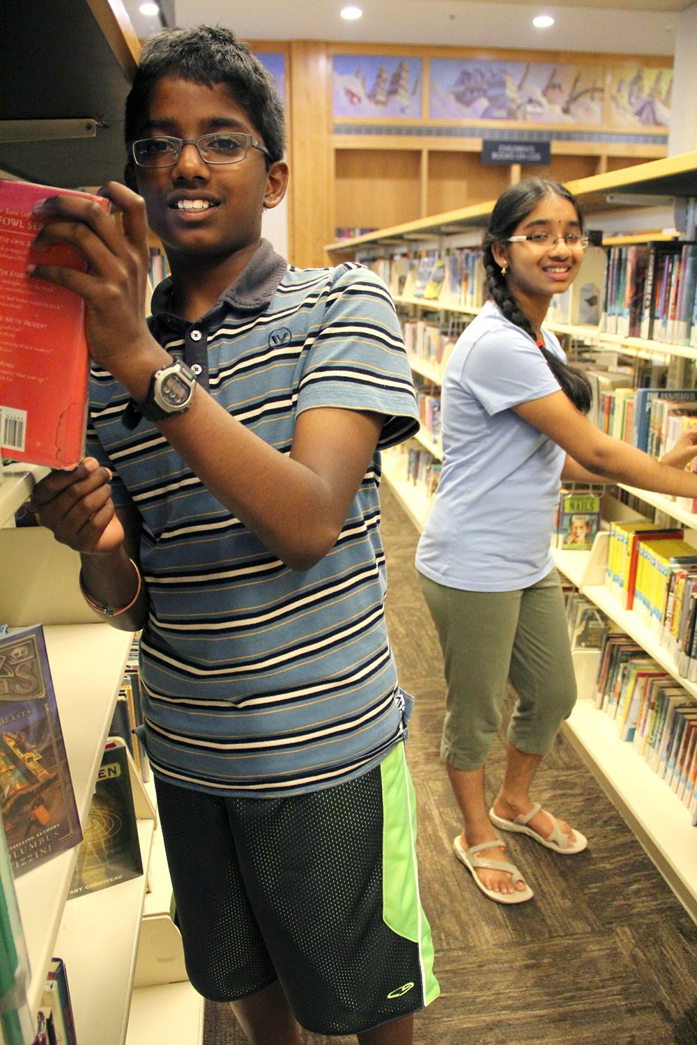 Photo of a young man and a young woman smiling and shelving library materials.