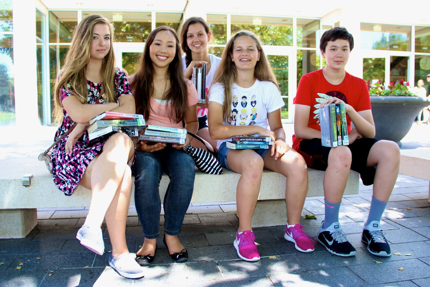 Photo of a group of young women and a young man holding books outside a library building.