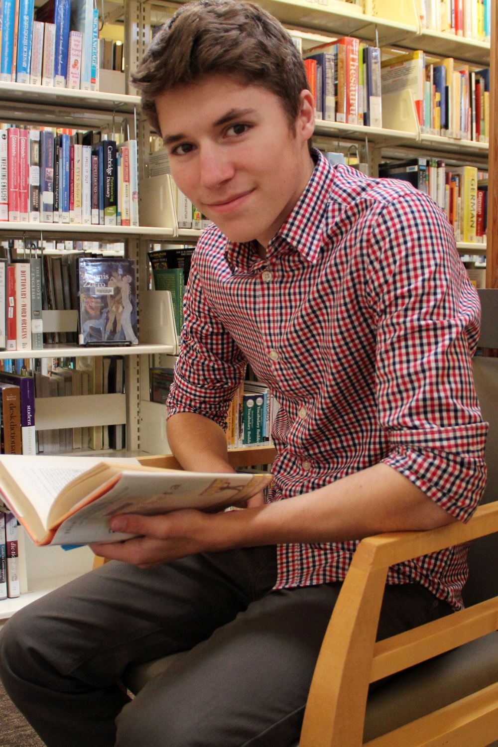 Photo of a young man smiling and holding a book in a chair inside a library.