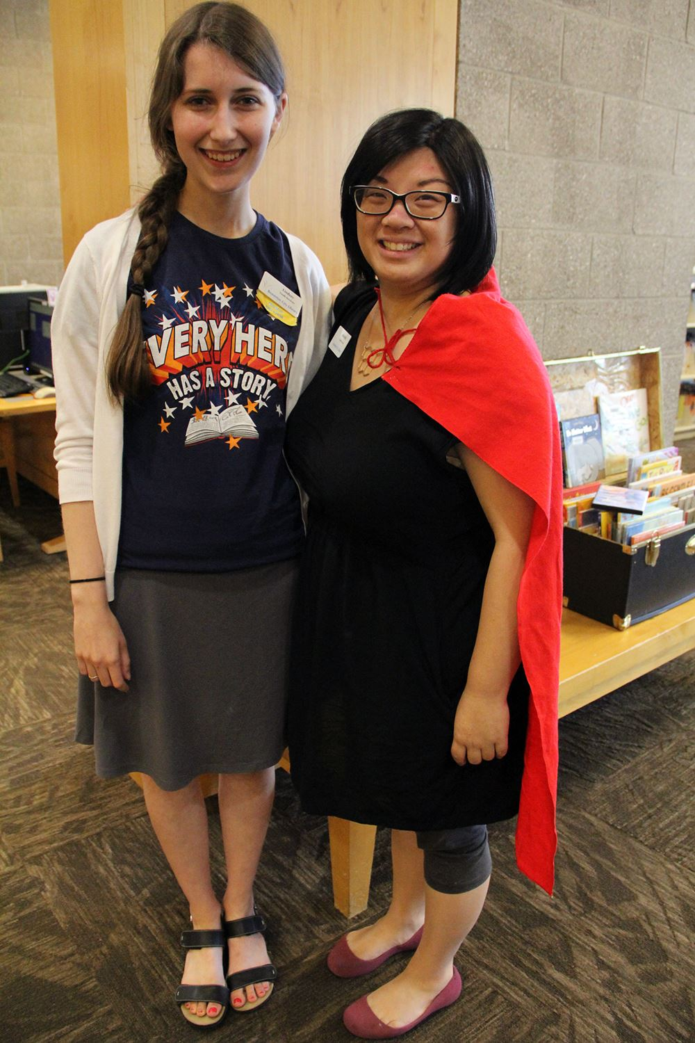 Photo of two women smiling and standing in a library.