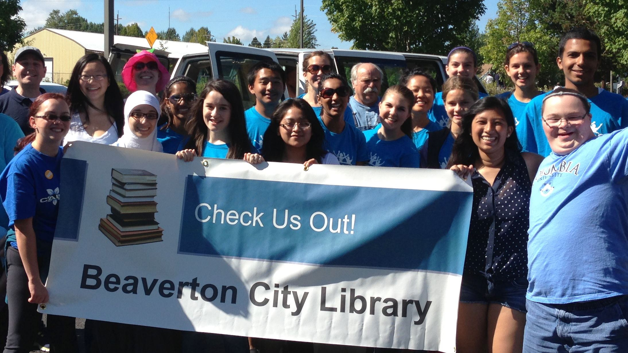 Photo of a group of people smiling and holding a banner promoting Beaverton City Library.
