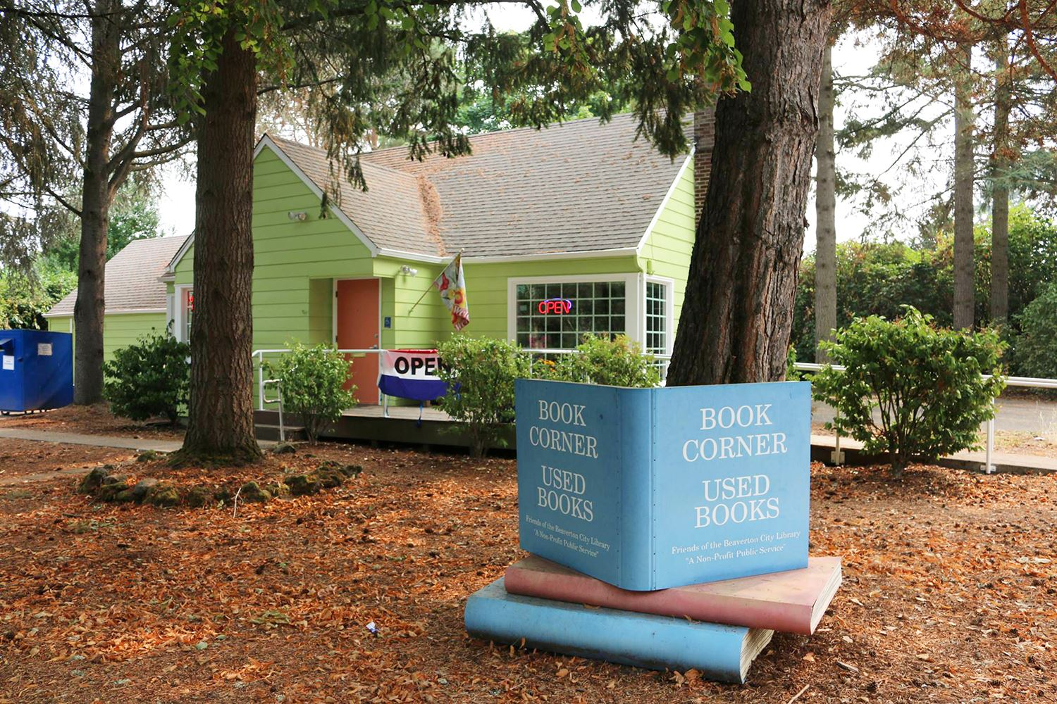 Photo of green house with large pink and blue books outside of it.